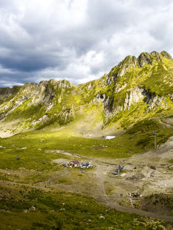 Epic mountain landscape. Beautiful natural terrain in the mountains, peaks and valleys, green meadow in the foreground