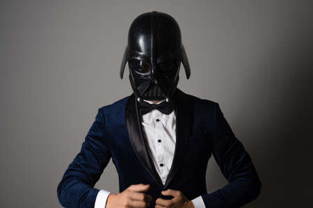 SAINT PETERSBURG, RUSSIA - SEPTEMBER 29, 2020: Respectable man in a tuxedo with a bow tie and a helmet of a combat star stormtrooper, business geek, illustrative editorial