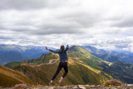 A young female tourist on top of a mountain jumps into the sky. Happiness and a sense of freedom, travel in the mountains, the power of nature