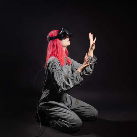 Virtual reality and futurism. Cyberpunk concept, a gamer with pink hair. Young woman in overalls and virtual reality glasses, is in a simulation, black background