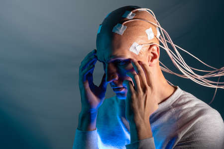 Contacts connected to the brain, reading brain signals, studying intelligence and brain activity. A bald man with electrodes in his brain
