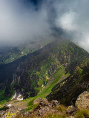 Beautiful mountain landscape. High-mountain massif, clouds over peaks. slope with rocks and grass in the foreground, a mountain range going into perspective, in the clouds.