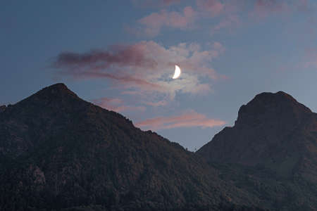 Moonlight in the mountains. Crescent moon in the sunset sky, pink clouds between two mountain peaks