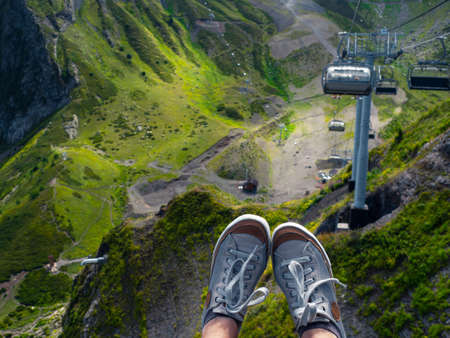 Mountain resort in summer, sneakers on the background of a mountain landscape, first-person photo. beautiful landscape, Infrastructure for traveling in the mountains. Chair lift. Cable car