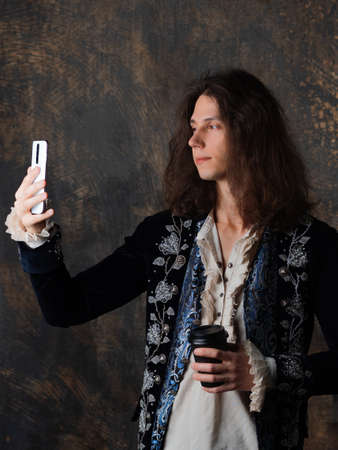 Digital Renaissance, concept. The guy is a gamer in a medieval costume and with a smartphone in hand, the blogger takes a selfie. Medieval style with a modern meaning, a mix of styles