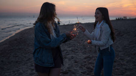Two young women with sparklers in the open air. Friends having fun on the beach,