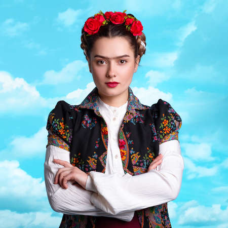 young woman in the image of the Mexican artist Frida with red roses in her hair.