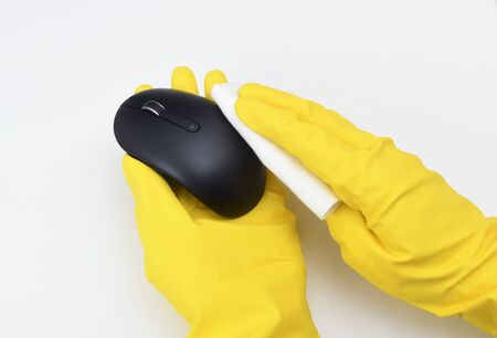 Disinfection in public places, the fight against the virus, coronavirus. A working hand wipes a computer mouse. A maid or housewife takes care of the house. Spring general or regular cleaning.