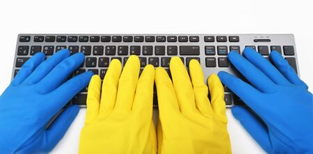 Four hands in bright rubber gloves are typing on the keyboard. Disinfection in public places, the fight against the virus, coronavirus.