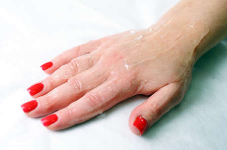 The female hand is covered with a liquid transparent gel before the laser procedure.