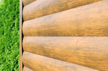 Metal lining on the facade of the building imitating the texture of wood.Element of the facade. Part of the facade decoration close-up. Facing material of buildings. Metal sheet roof. Stock Photo