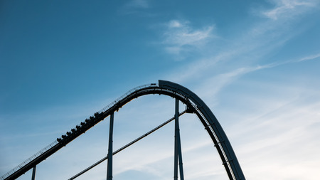 A roller coaster going up the tracks against a blue sky