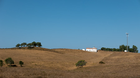 A building in a landscape surrounded by dry, brown grass