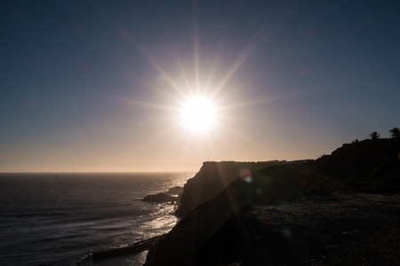 The sun setting behind cliffs by the ocean in Portugal