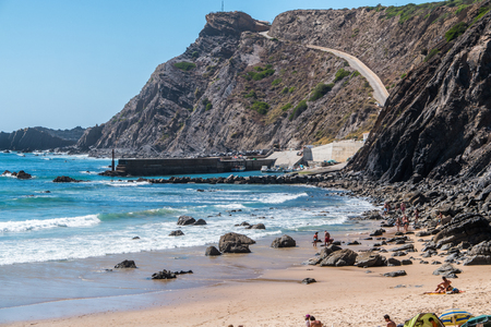 A road going up a cliff next to a beach in Portugal
