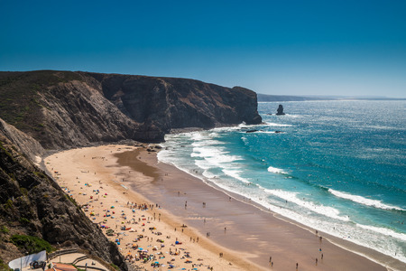 A portuguese beach in a bay surrounded by cliffs