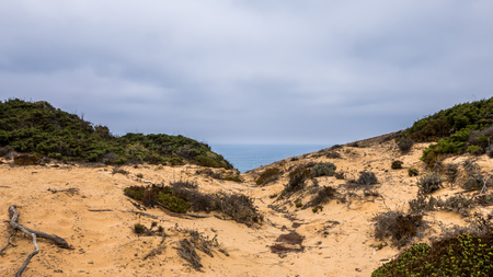 Ocean in the background and sand in the foreground in Portugal Stock Photo
