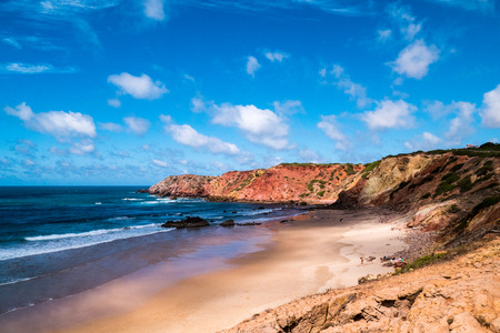 A portuguese beach in a bay surrounded by cliffs and the ocean
