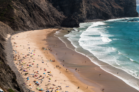 People sunbathing on a beach in a bay in Portugal during summer