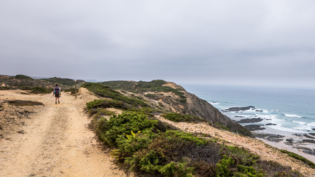 A lonely hiker walking along a sand path next to the ocean in Portugal Stock Photo