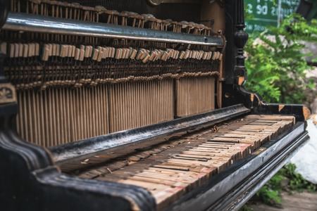 Old abandoned broken piano on the street under the open sky