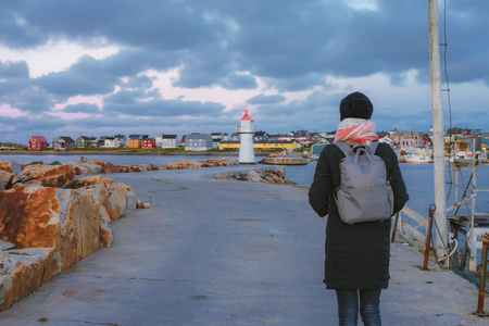 The girl with a grey backpack going to the beacon on the mooring in Vardo, Norway Stock Photo