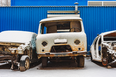 the old rusty broken cars on a dump under snow