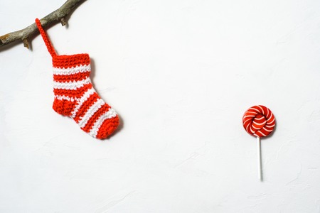Christmas sock in a white-red strip hanging on a branch and red lollipop on a white background Stock Photo