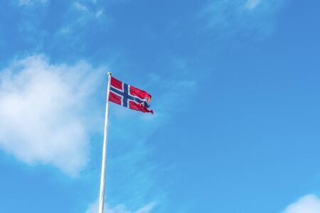 Flag of Norway on a background of blue cloudy sky