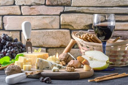 Still life with different varieties of cheese on wooden plate Banco de Imagens