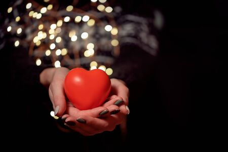 Red heart holding in the women arms with light bokeh. Congratulations on Christmas and Valentine s Day