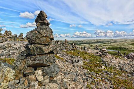 Touristic pyramid balanced stack of stones at the summer tundra. Way to Teriberka, Kola Peninsula