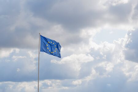 Official flag of European Union in the sky. Circle of yellow stars on blue background