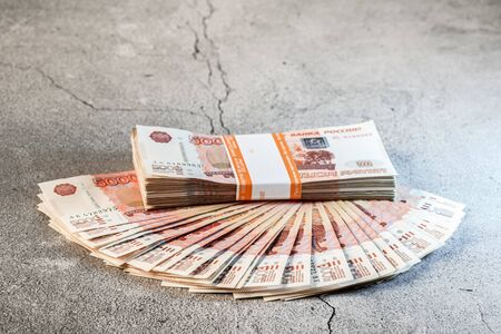 Large stack and fan of banknotes, Russian rubles laying on a grey concrete surface