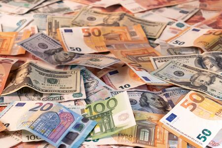 Background made of dollar, euro and russian roubles banknotes on a table