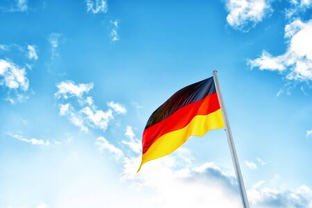 A German flag with black, red and yellow stripes in front of clouds in blue sky