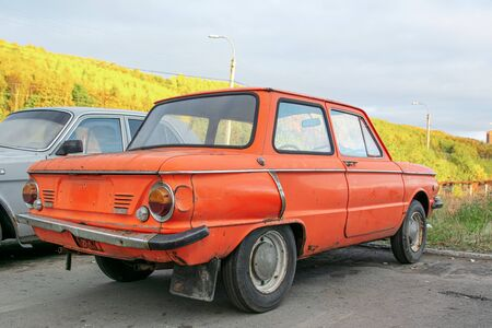 Soviet retro car . Old red rusty and dirty retro automobile back view. Without trade mark