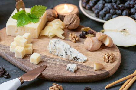 Cheese plate from different kind of cheese - Emmental, Homemade, Parmesan, blue cheese, bread sticks, walnuts, raisin, pear, grapes on black table