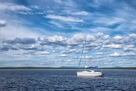 Blue pacific lake with boat with russian flag in boreal forest in sunny day with many beautiful clouds Stockfoto