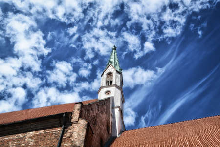 Riga, Latvia - June 11, 2016: View from below to the roofs of houses and to the tower with a spire in the center of the Riga