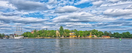 STOCKHOLM SWEDEN - AUGUST 2, 2019: Panoramic view on coastline of Skeppsholmen island with boats and ships and cloudy sky Redactioneel