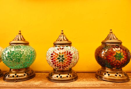Oriental turkish lanterns at the street market on a yellow wall background Stockfoto
