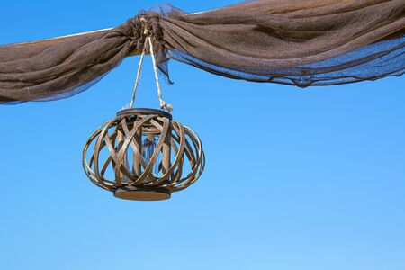 An old wooden lantern hanging on the rope with baggy curtains against a blue clear sky