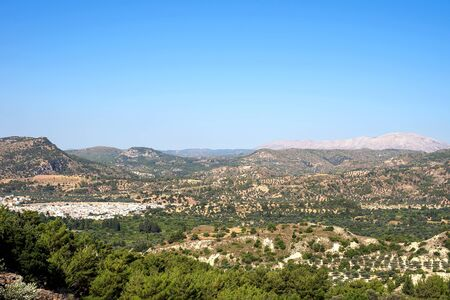 Rhodes island scenery on a sunny summer day with dry trees, green fields, brown soil and blue clear sky with haze