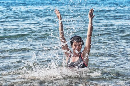 Happy young woman in in a splash of sea waves, raising her hands