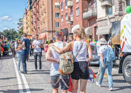 Stockholm, Sweden - August 2, 2019: People on the street prepairing to a Pride parade. Two girls hug by the shoulders view from the back
