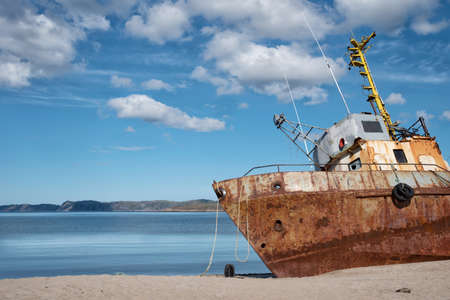 Rusty old abandoned iron fishing boat which is pulled out on the coast of the sea in Teriberka Stockfoto