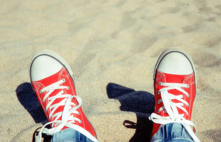 Two legs in a red gym-shoes with white laces, against the background of light beach sand on a sunny day Stockfoto