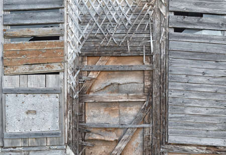 Old wooden walls with plaster crossed base with window covered with boards. Old wooden window structures with rusty nails. Wooden house wall vintage designs. Beams with a crate of thin strips. Stockfoto