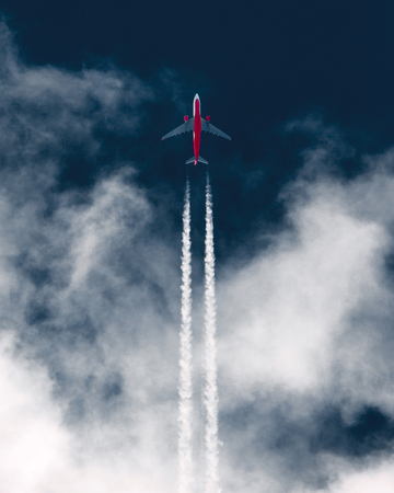 Airplane in the sky leaving contrails